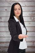 stock photo of presenting  - Pretty businesswoman presenting with hand against wooden planks - JPG