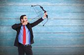 foto of bow arrow  - Focused businessman shooting a bow and arrow against wooden planks - JPG