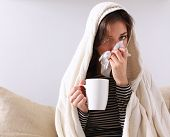 stock photo of couch  - Sick woman covered with blanket holding cup of tea sitting on sofa couch - JPG