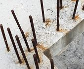 stock photo of reinforcing  - Grey concrete blocks with rusty reinforcing bars - JPG