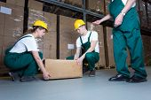 stock photo of blue-collar-worker  - Two young workers lifting heavy box in warehouse - JPG