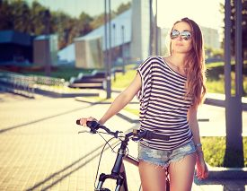 foto of urbanization  - Trendy Hipster Girl with Bike on Urban Background - JPG