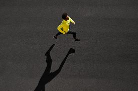 stock photo of sprinters  - Top view athlete runner training at black road in yellow sportswear at central position - JPG