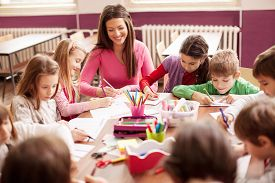 stock photo of teachers  - Pupil boys and girls sitting together around the table in classroom and drawing - JPG