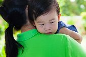 foto of comfort  - Mother carrying and comfort her daughter in backyard over blur green nature background little asian girl  - JPG