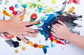 foto of finger-painting  - Closeup of little children hands doing finger painting with various colors on white background art education and creativity concept top view - JPG