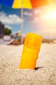 pic of suntanning  - Closeup shot of yellow suntan lotion bottle lying on sand at beach - JPG