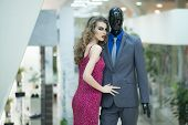 picture of dress mannequin  - Sexy young girl with bright makeup and curly hair standing with male mannequin in formal clothes on shopping background horizontal picture - JPG