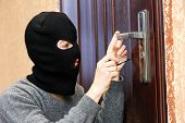 stock photo of delinquency  - Burglar breaking into house - JPG