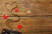image of heart sounds  - Audio cassette with magnetic tape in shape of heart on wooden background - JPG