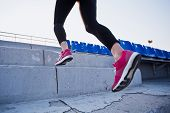 stock photo of upstairs  - Sporty woman legs with sneakers running upstairs of a stadium between stands. Sports, motivation and running concept. Conceptual photo. Copy space. Concrete steps ** Note: Shallow depth of field - JPG