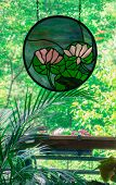 image of glass frog  - stained glass of pink water lilies with red eyed frog hanging in window with deck and woods in the background - JPG