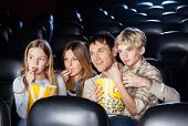 pic of watching movie  - Family of four eating popcorn while watching film in movie theater - JPG