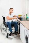 picture of handicapped  - Young Handicapped Man On Wheelchair Cleaning Induction Stove - JPG