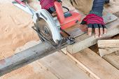 pic of sawing  - Man carpenter cutting wood with electric saw for Home Building - JPG