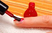 picture of nail  - Red nail polish applied to the nail of hand manicure process nail care - JPG