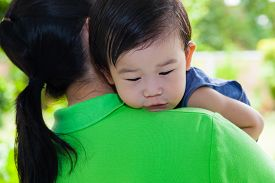 foto of cry  - Mother carrying and comfort her daughter in backyard over blur green nature background little asian girl  - JPG