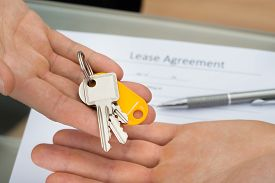 stock photo of rental agreement  - Person Holding Key Above Man - JPG