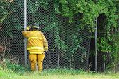Fireman Peering Through Fence