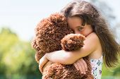 Cute little girl embracing her new teddy bear and looking at camera. Portrait of lovely female child poster