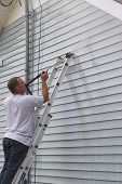 picture of pressure-wash  - Contractor pressure washing house removing mildew  - JPG