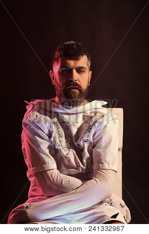 poster of Halloween Man Wrapped In White Clothes. Mummy Hipster Sitting On Brown Background. Insane, Lunatic O