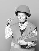 Young Cute Funny Builder Boy In Orange Uniform And Hard Hat Or Helmet With Glasses Holding Tool Or P poster