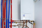 Pipes and boiler of gas heating system in the house poster