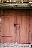 Old Wooden Door Closed On The Lock. Peeling Paint. House. Barn. Doors Red. The Door To The Hinges. poster