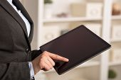 Business woman below chest using tablet in a homey environment poster