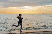 Confident Sports Girl Jogging On The Seafront At Sunset, Listening To Music On Headphones poster