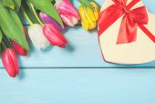 Colorful Spring Tulip Flowers With Decorative Giftbox On Light Blue Wooden Background As Greeting Ca poster