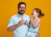 Happy Fathers Day! Funny Dad And Daughter With Mustache Fooling Around On Yellow Background poster
