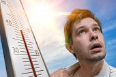 Hot Weather Concept. Young Man Is Sweating. Thermometer Is Showing High Temperature. Sun In Backgrou poster