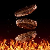 Flying beef minced hamburger pieces above grill flames, isolated on black background. Concept of fly poster