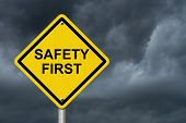 Safety First Warning Sign, Yellow Warning Sign With Words Safety First Warning With Stormy Sky Backg poster