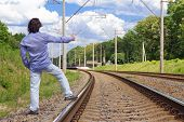Man Hitch-hiking On A Train Tracks