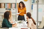 Young Adult Woman With Curly Hair Making Presentation To Her Attentive Colleagues At Meeting poster