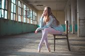 Photo Of Ballerina While Shes Sitting On The Chair In An Old Building. Young, Elegant, Graceful Woma poster
