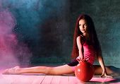 Young Graceful Long Haired Girl Gymnast Doing Gymnastic Exercises With Ball Sitting On The Floor Str poster