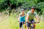 Happy couple riding bicycles outside, healthy lifestyle fun concept. mountain bike fitness outdoor e
