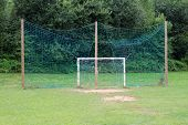 White Dilapidated Goal Post For Soccer Practice With Partially Broken Net In Front Of Large Green Pr poster