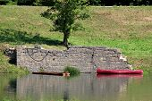 Wooden River Boat Next To Dilapidated Dark Red Plastic Canoe Boat Tied To Old Ruins Of Stone Wall At poster