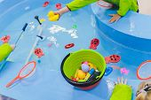 Fishing In The Paddling Pool. Childrens Toys In The Pool. Toy Fish Fishing Rod. Cheerful Children Fi poster