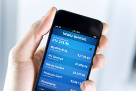 picture of save money  - A man holding smartphone with mobile banking application on a screen - JPG