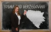 Teacher Showing Map Of Bosnia Herzegovina On Blackboard