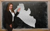 Teacher Showing Map Of Liberia On Blackboard