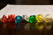 stock photo of tetrahedron  - Multicolored role play dice on wooden table top with a map in the background - JPG