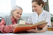 stock photo of hospice  - Senior woman and nurse looking together at album with old photographs - JPG