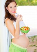 foto of expecting baby  - Beautiful expectant girl eat fresh vegetable salad - JPG